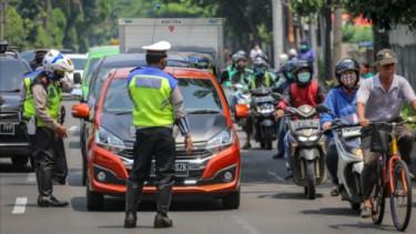 Petugas kepolisian menghentikan kendaraan yang melintas saat PSBB
