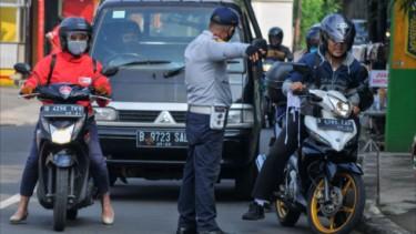 Petugas Kepolisian memeriksa kendaraan yang melintas saat PSBB